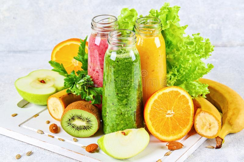 Green, yellow, purple smoothies in currant bottles, parsley, apple, kiwi, orange on a gray table. royalty free stock image