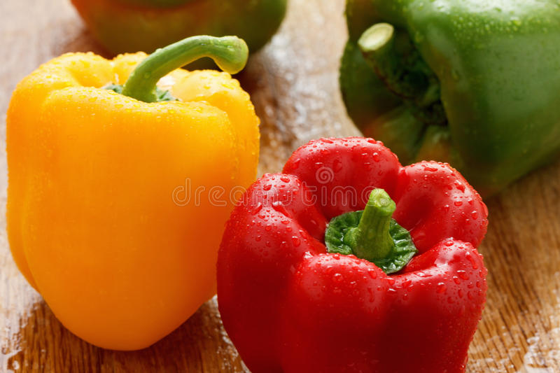 Green , yellow and red bell pepper with water drops closeup stock images