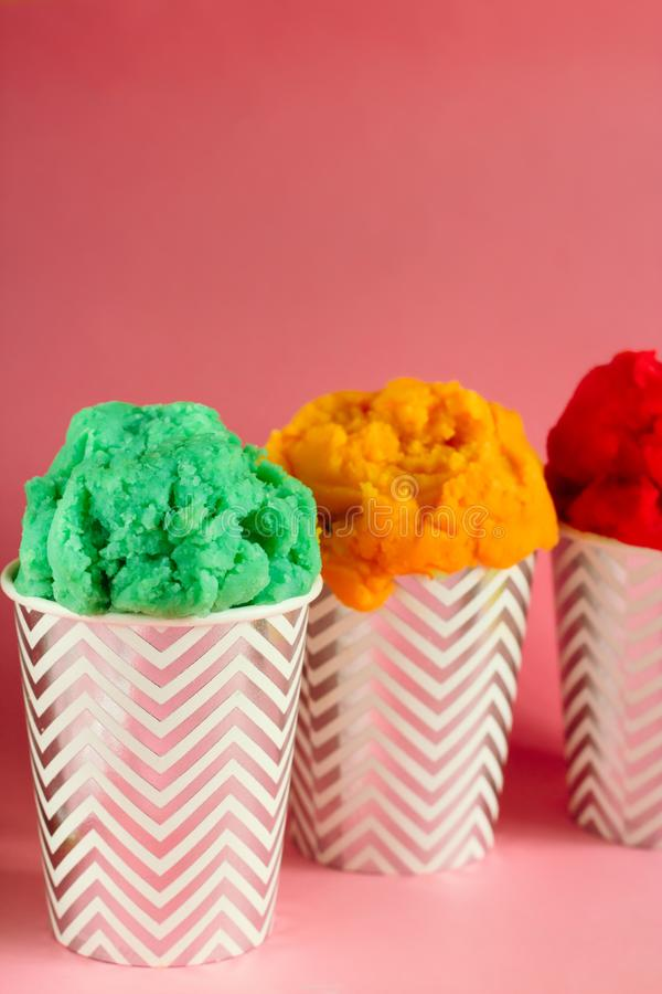 green,yellow and red fruit ice cream or frozen yogurt in stripped cups stock images