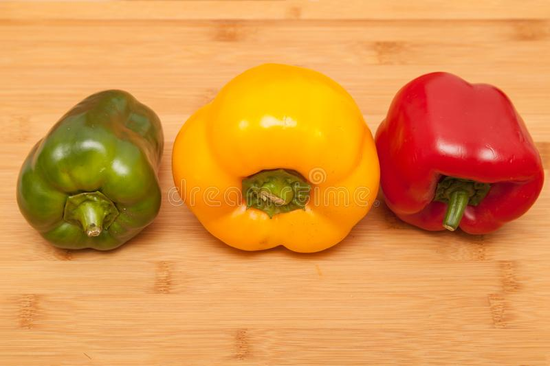 Green, yellow and red pepper on wooden background. Close up of Green, yellow and red pepper on wooden background stock photography