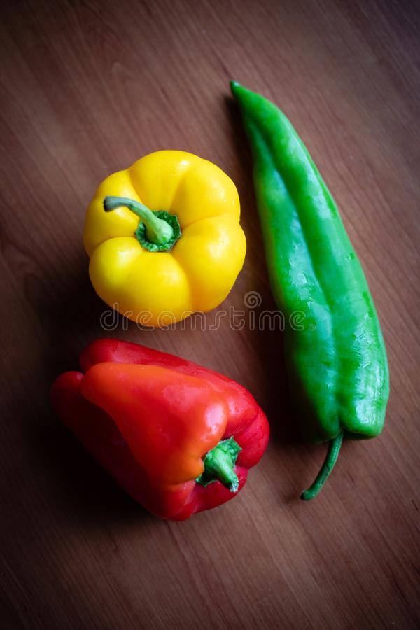 Green, yellow and red peppers on wooden table at home. Green, yellow and red peppers on wooden table closeup shot royalty free stock photos