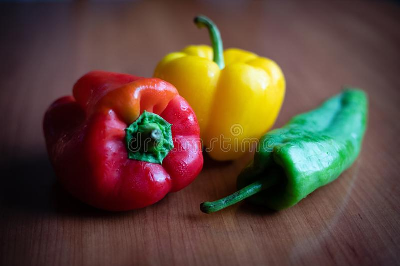 Green, yellow and red peppers on wooden table at home. Green, yellow and red peppers on wooden table closeup view royalty free stock photos