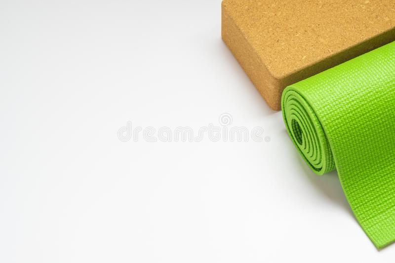 Green Yoga mat and yoga blocks for Yoga, Pilates exercise at home or gym rolled on white background. Yoga practice, relaxation and stock photo