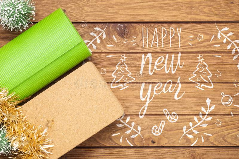 Green yoga mat or pilates mat and  block with Christmas tree ornaments decoration on wood for Merry Christmas and Happy new year stock photo