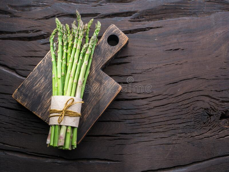 Green young asparagus sprouts on wooden table. Top view stock photos