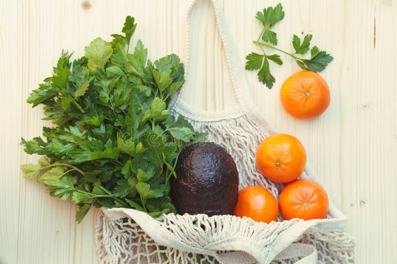 White eco-friendly reusable string bag with fresh fruits, herbs and vegetables, avocado, parsley, oranges on wooden background. Green zero waste lifestyle, white royalty free stock image