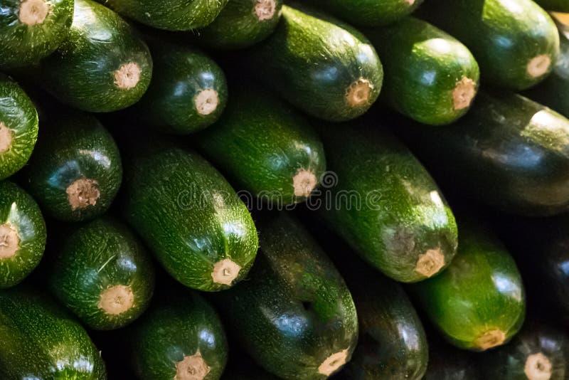 Green zucchini horizontal long fruit stack of vegetables shiny skin background market tray royalty free stock photos