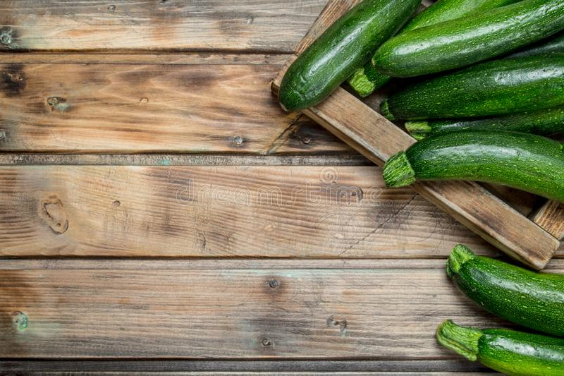 Green zucchini in wooden tray. On wooden background royalty free stock images