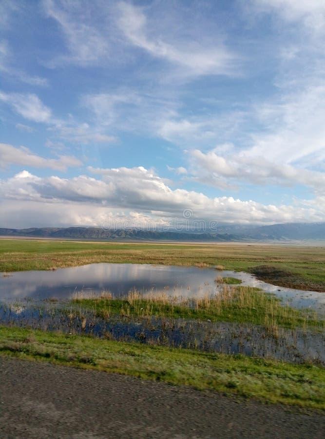 Greenfield moln, blå himmel, berg, waterpool, gräs, stäpp, väg, arkivfoton