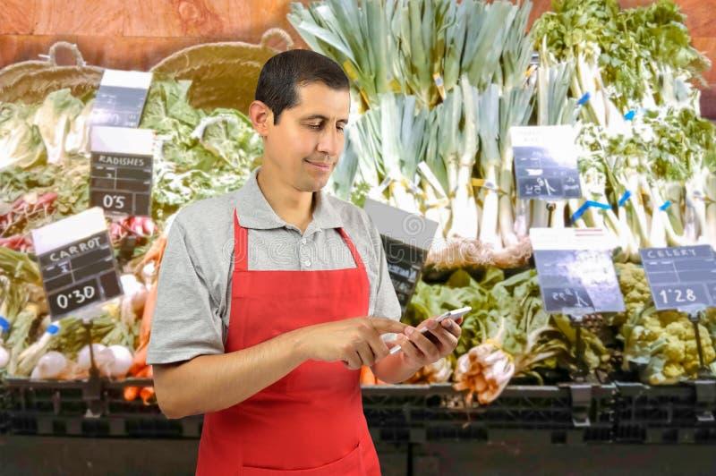 Greengrocer используя smartphone стоковые изображения