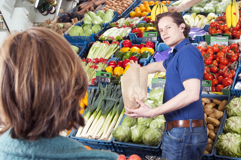 Greengrocer. Green grocer serving a customer, filling a brown paper bag with peppers royalty free stock photo