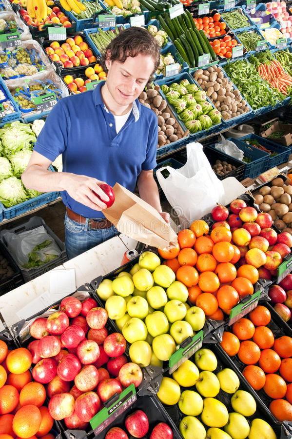 Greengrocer. Green grocer putting red apples in a brown paper bag stock photos