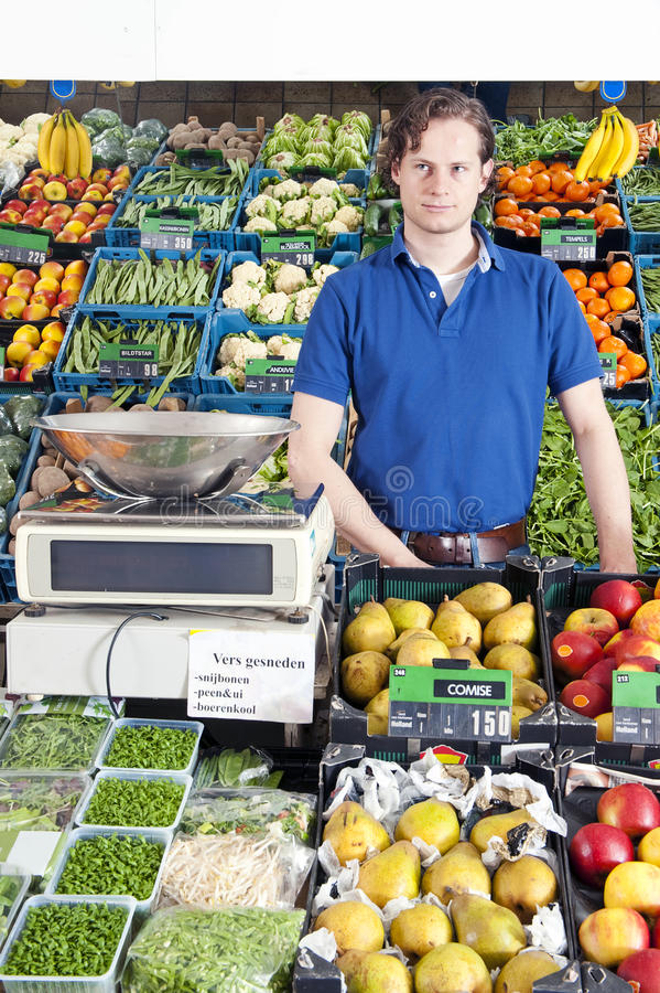Greengrocer. A greengrocer standing behind the display counter surrounded by fresh fruit and vegetables stock photo