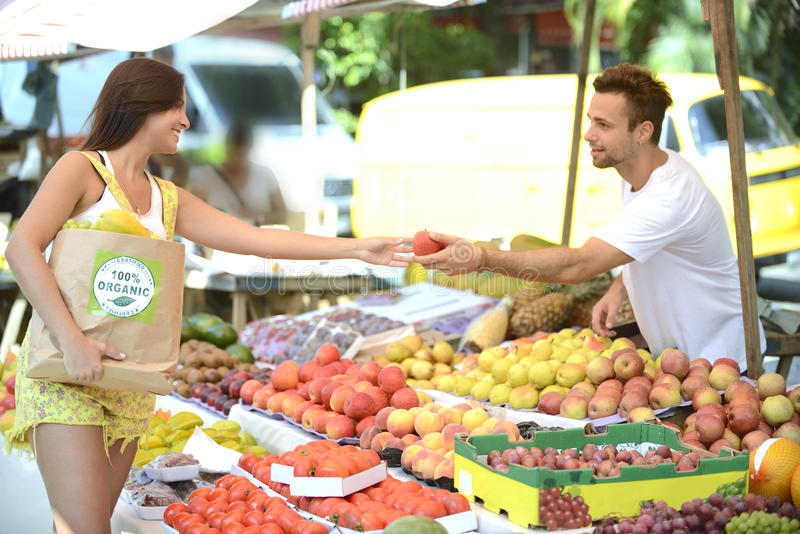 Greengrocer handing out a fruit to a consumer. stock image