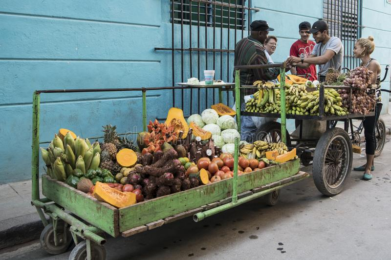 Fruit and vegetable vendor in front of turquoise house in street of Habana, Cuba royalty free stock images