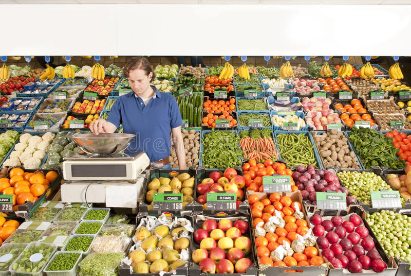 Greengrocer at work. A green grocer weighing vegetables in a grocery shop stock photos
