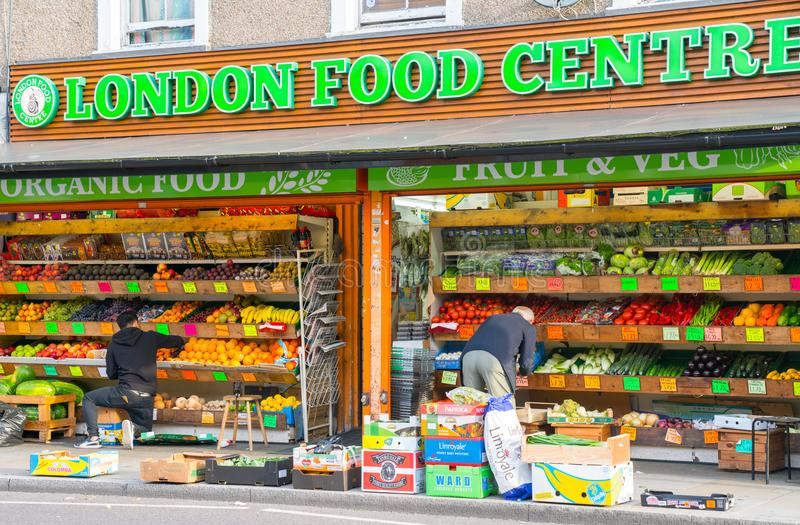 Greengrocers stocking fruit and vegetables shelves outside thier shop on Roman Road in Bow London, England. royalty free stock image