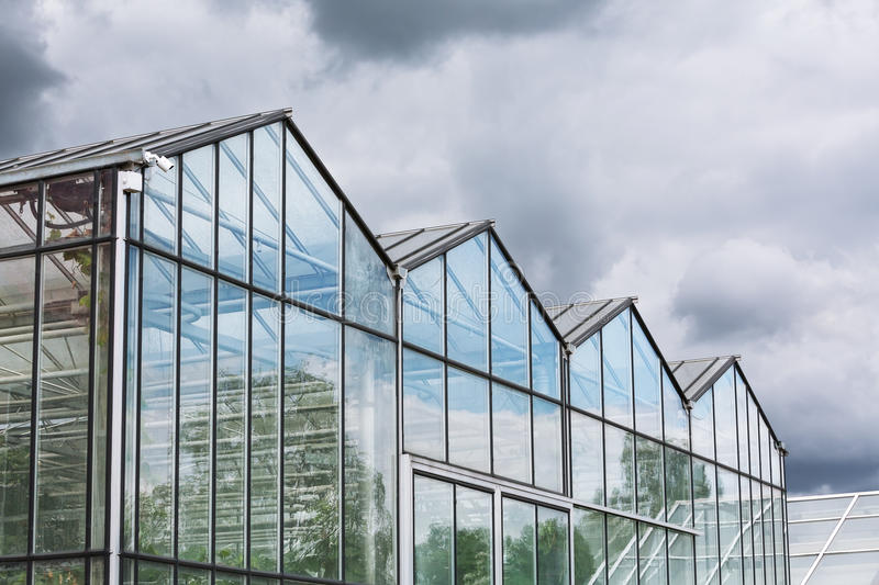 Greenhouse against dark cloudy sky stock image