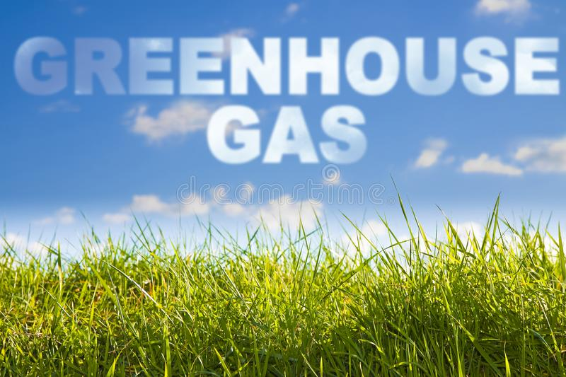 Greenhouse gas emissiones concept image against a green wild grass on sky background stock image