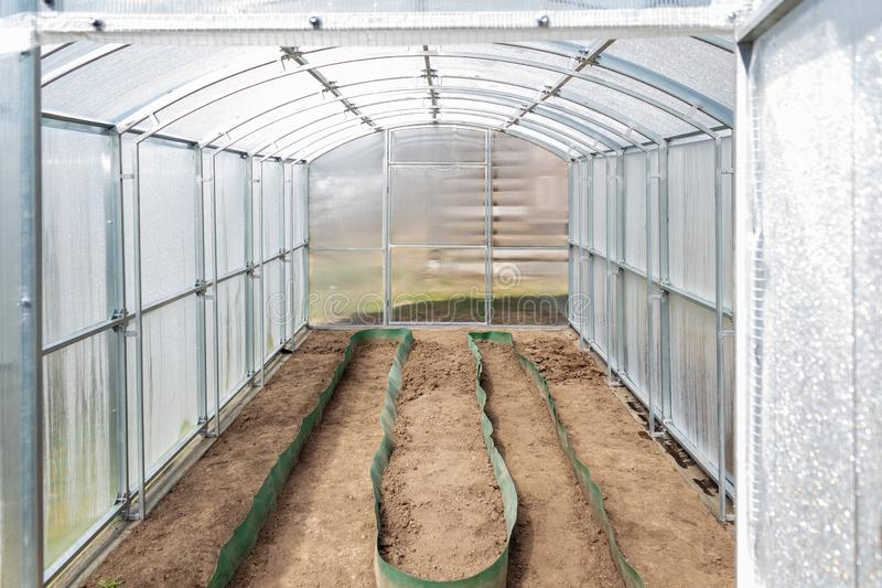 The greenhouse made of polycarbonate on the dacha plot is ready for spring planting. Tula region, Russia. The greenhouse made of polycarbonate on the dacha plot stock photos