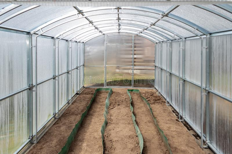 The greenhouse made of polycarbonate on the dacha plot is ready for spring planting. Tula region, Russia. The greenhouse made of polycarbonate on the dacha plot stock photo
