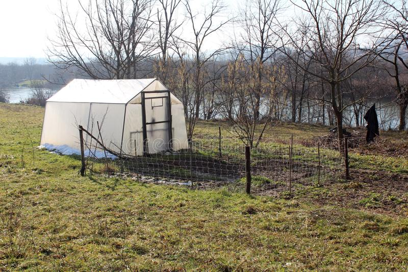 Greenhouse with small garden next to river on cold winter day royalty free stock photo