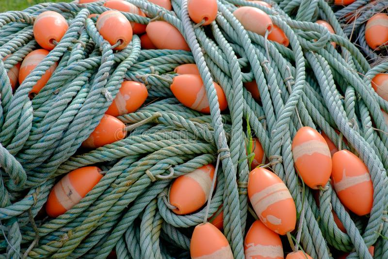 Green fishing net ropes with orange floats stock photo