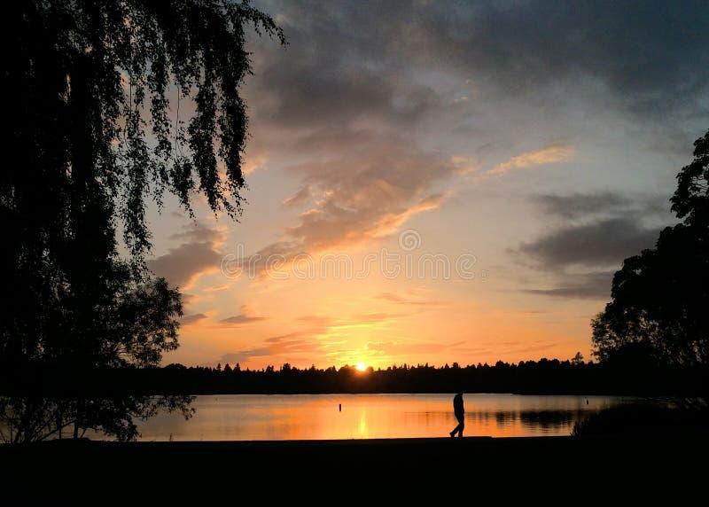 Greenlake Sunset. Sun gives one final peek as it tucks itself away behind Phinney Ridge stock photography