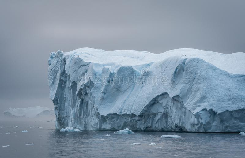 Greenland. The biggest glacier on a planet Jakobshavn. Huge icebergs of different forms in the gulf. Studying of a. Phenomenon of global warming and stock photos