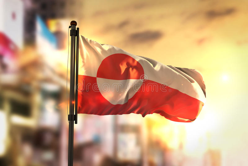 Greenland Flag Against City Blurred Background At Sunrise Backlight royalty free stock images