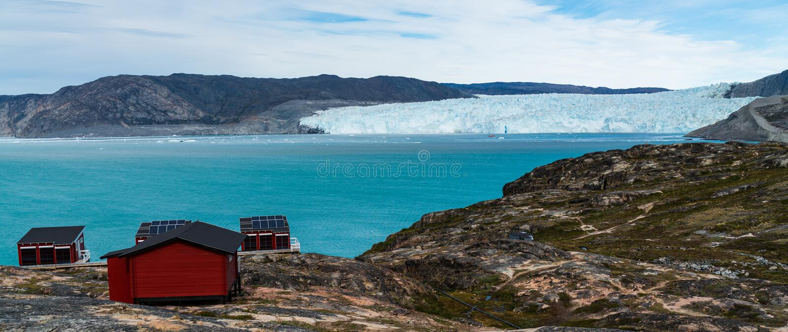 Greenland glacier nature landscape with famous Eqi glacier and lodge cabins. Tourist destination Eqi glacier in West Greenland AKA Ilulissat and Jakobshavn stock photography
