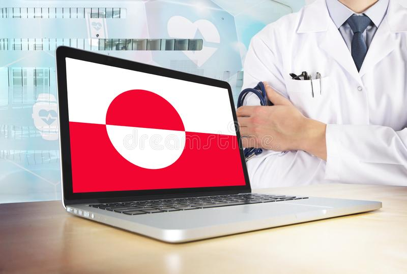 Greenland healthcare system in tech theme. Flag on computer screen. Doctor standing with stethoscope in hospital. Cryptocurrency. And Blockchain concept stock photo