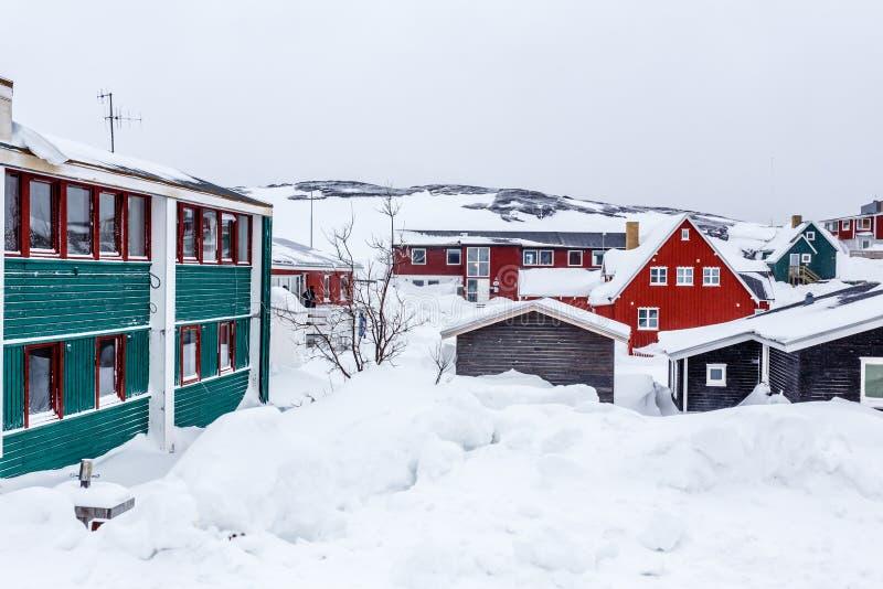 Greenlandic Inuit-huizen onder behandeld in sneeuw een voorstad van arct royalty-vrije stock afbeelding