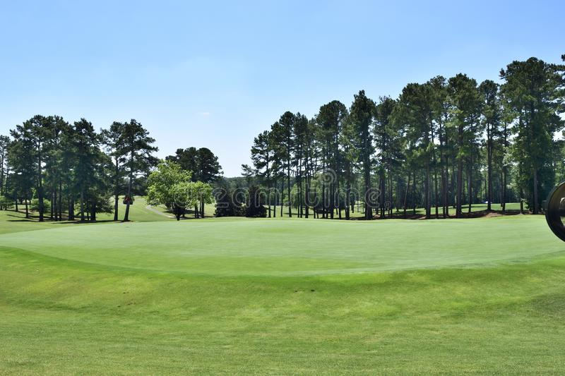 Greens and fairway on golf course, Georgia, USA. Empty tree lined greens and fairway of golf course in Georgia, USA on sunny day with blue skies royalty free stock photos