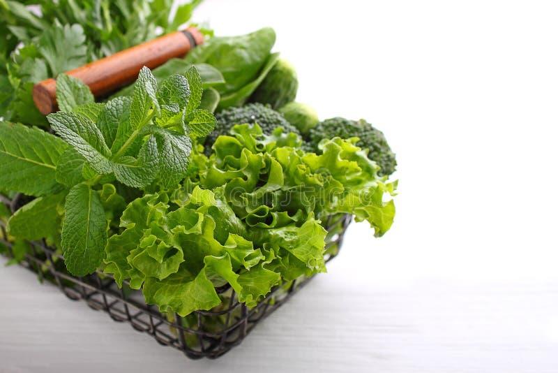 Greens: spinazie, komkommer, broccoli, knoflook, munt, peterselie, sla, uien in een metaalmand stock foto