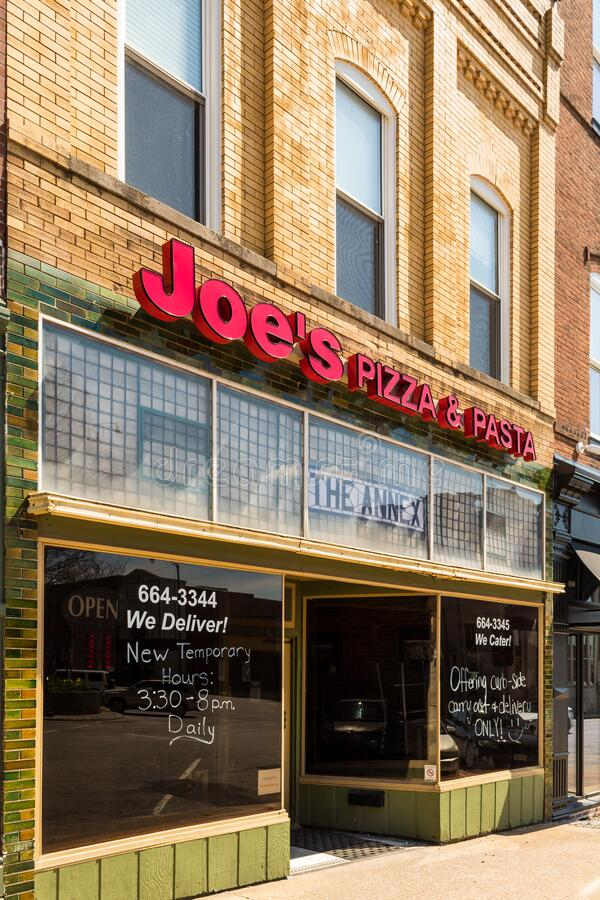 Small town pizza joint in the Midwest United States opens only for limited hours. GREENVILLE, ILLINOIS/USA - APRIL 01, 2020: Small town pizza joint in the stock photography
