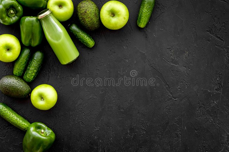 Greeny vegetable smoothie in bottle with cucumber, pepper, apple on black background top view mock up royalty free stock photos