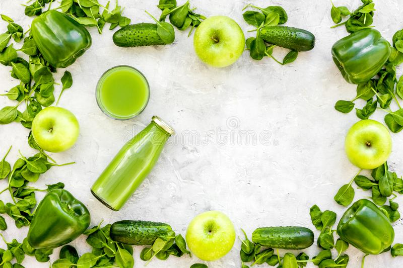 Greeny vegetable smoothie in bottle with cucumber, pepper, apple, celeriac on stone background top view mock up stock photo