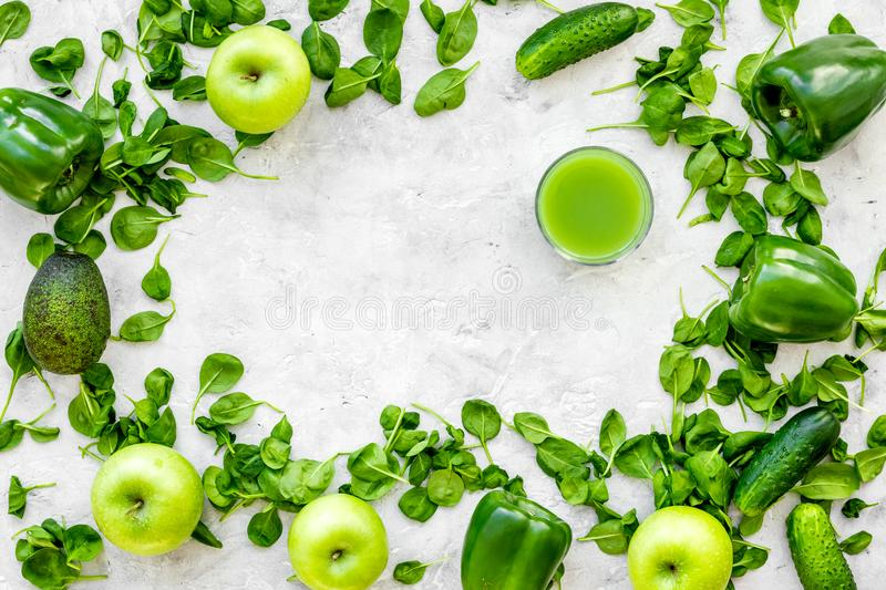 Greeny vegetable smoothie in glass with cucumber, pepper, apple, celeriac on stone background top view mock up stock image