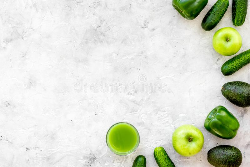 Greeny vegetable smoothie in glass with cucumber, pepper, apple on stone background top view mock up stock photo