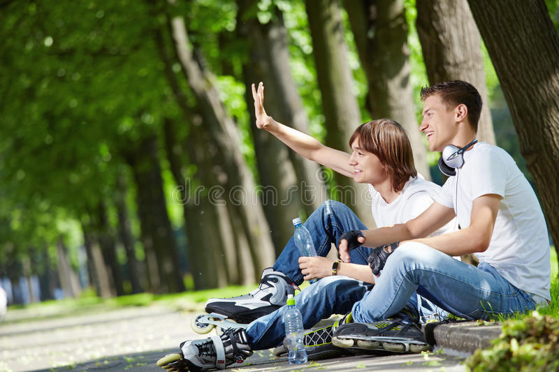 Greet. Young people with rollers have a rest on a border stock photography