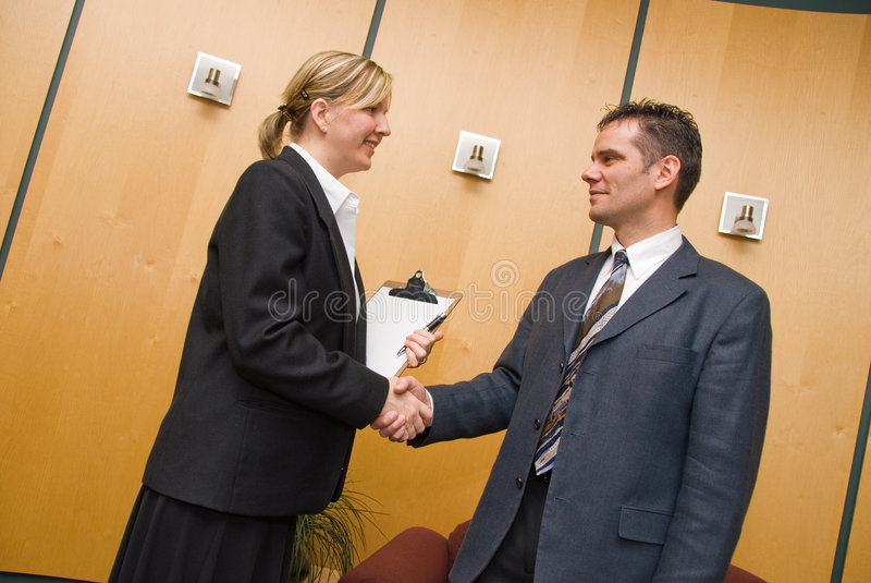 Greeting. Man and woman greeting each other in a reception area royalty free stock photos