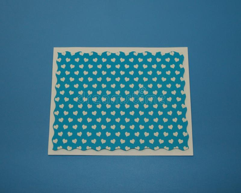 Greeting card blue rectangle with wavy border, and a pattern of small white hearts stock image