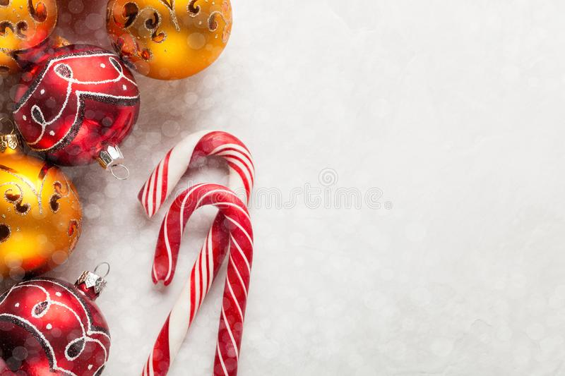Greeting card with Christmas decorations in red and gold balls, snow and candy canes on a white concrete background. Top stock photos