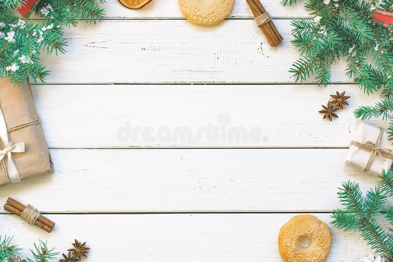 Greeting card. Christmas gifts, pine cones, fir branches, spruce, cookies, lights, oranges, cinnamon, snowflakes and festive tinse. Christmas gifts, pine cones stock image