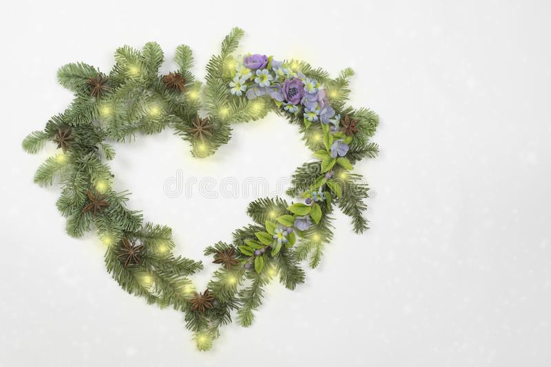 Christmas wreath in heart shape with flowers stock photos