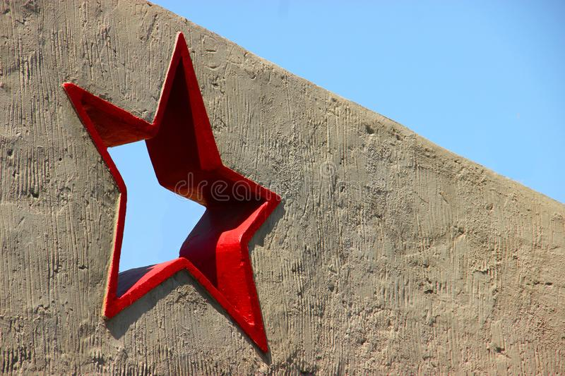 Greeting card with the day of the defender of the fatherland. February 23. red five-pointed star in a concrete wall against a blue. Blue sky. Victory day. Mock royalty free stock photography