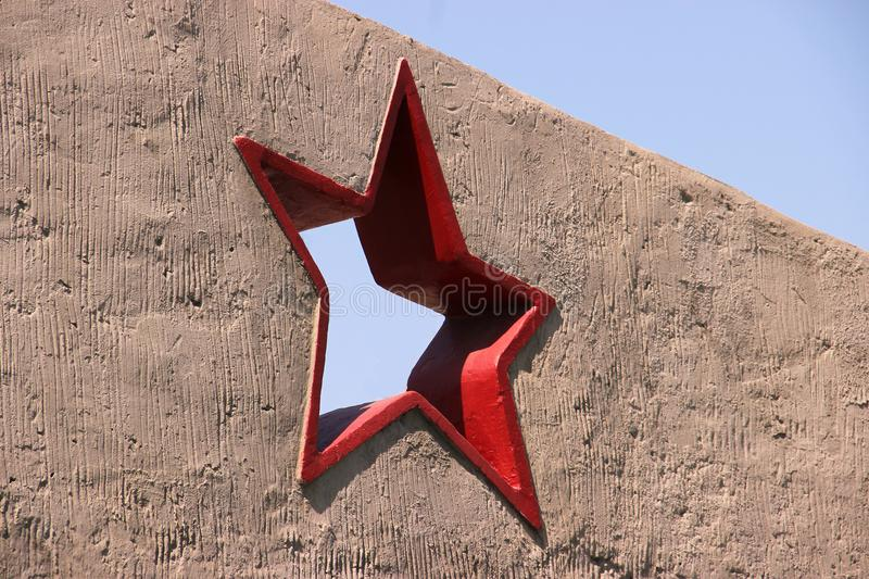 Greeting card with the day of the defender of the fatherland. February 23. red five-pointed star in a concrete wall against a blue. Blue sky. Victory day. Mock royalty free stock image