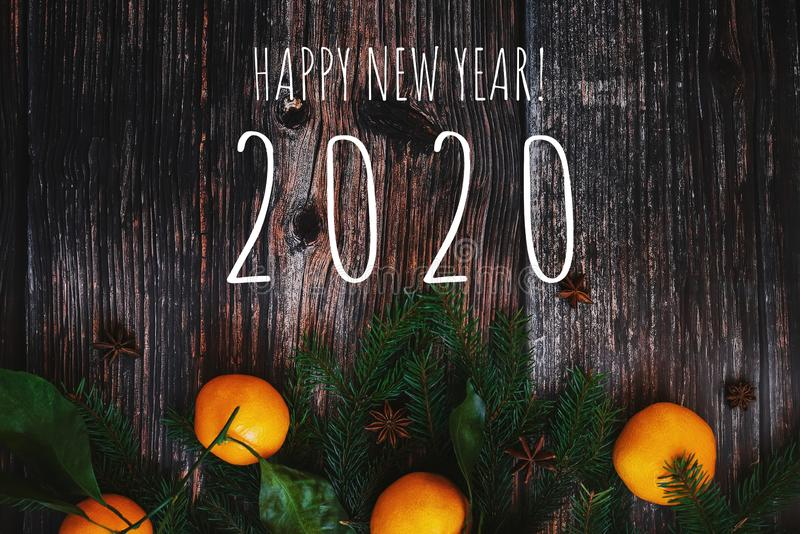 Fir branches and tangerines on a wooden background and the text Happy New year 2020. Greeting card with fir branches and tangerines on a wooden background and royalty free stock photography