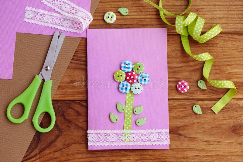 Greeting card with a flower made of wooden buttons, decorated with lace. Beautiful paper card crafts for mom`s birthday. Mothers day cards to make in school royalty free stock images